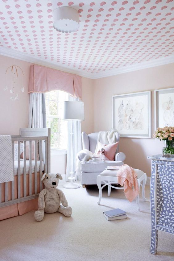 a simple pastel nursery with blush walls, grey and blue furniture, a printed ceiling, pastel pink textiles and bedding and a gallery wall