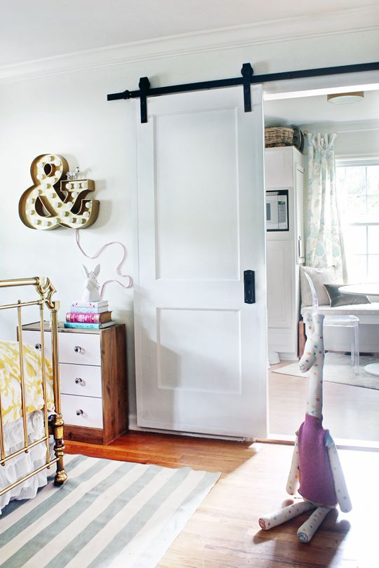 a simple white sliding door saves space in a small nursery and matches the interior very well
