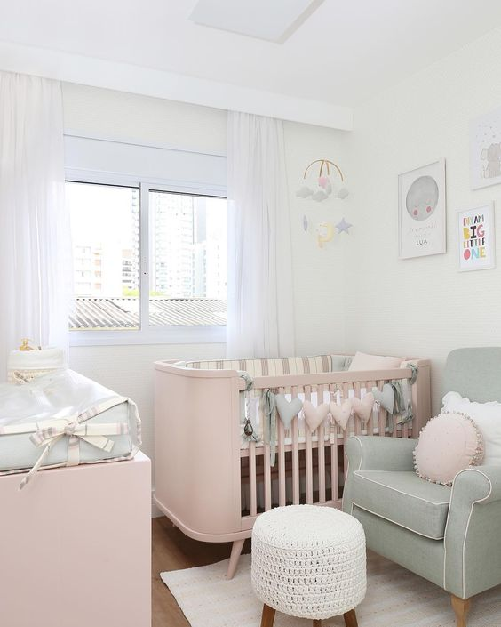 a small and pretty baby nursery with pastel furniture, a pastel heart garland, neutral textiles and a bright gallery wall