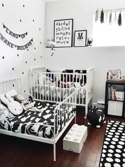 a small black and white shared room with some fun prints, cute toys and textiles plus a bunting