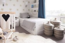 a soothing neutral shared room with a star print wall, some neutral furniture and cozy layered rugs