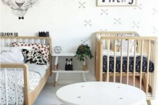 a stylish Scandinavian shared room done in black and white, with wooden furniture, pastel tbles and lots of prints