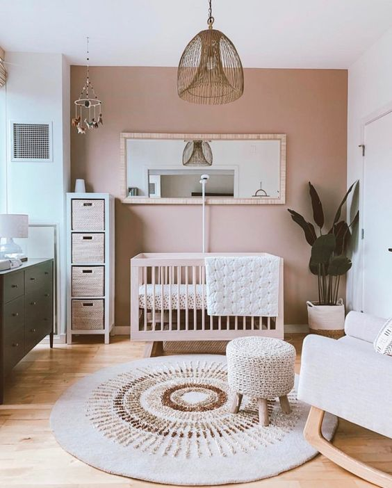 a stylish boho nursery with a pink accent wall, neutral furniture, a green dresser, a wicker pendant lamp and neutral textiles