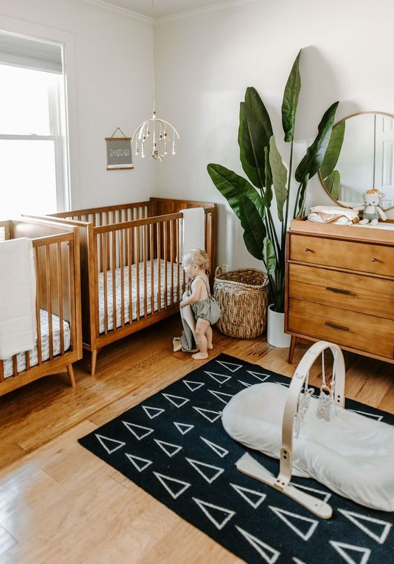 a stylish mid-century modern nursery with rich-stained furniture, a basket, a statement plant and a cool printed rug