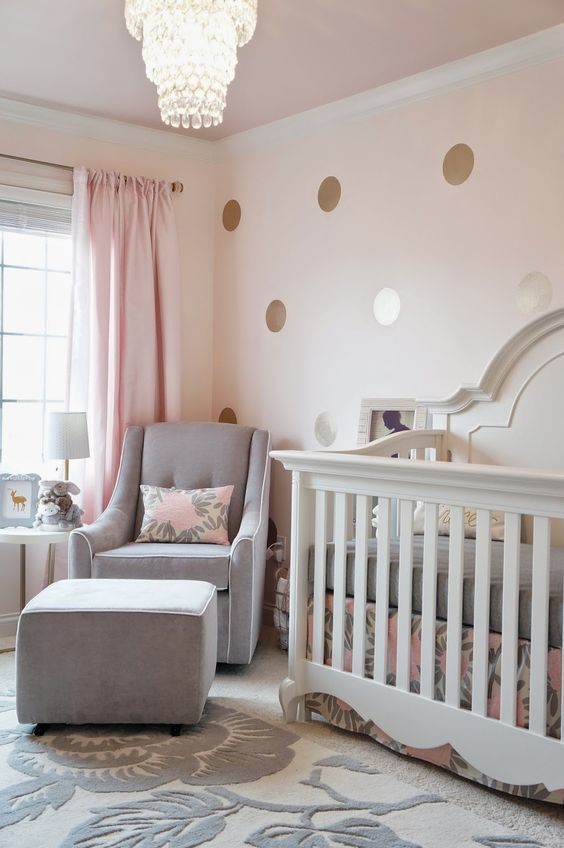 a stylish modern girl nursery with a polka dot wall, a white crib and a grey chair with an ottoman, a crystal chandelier and grey bedding