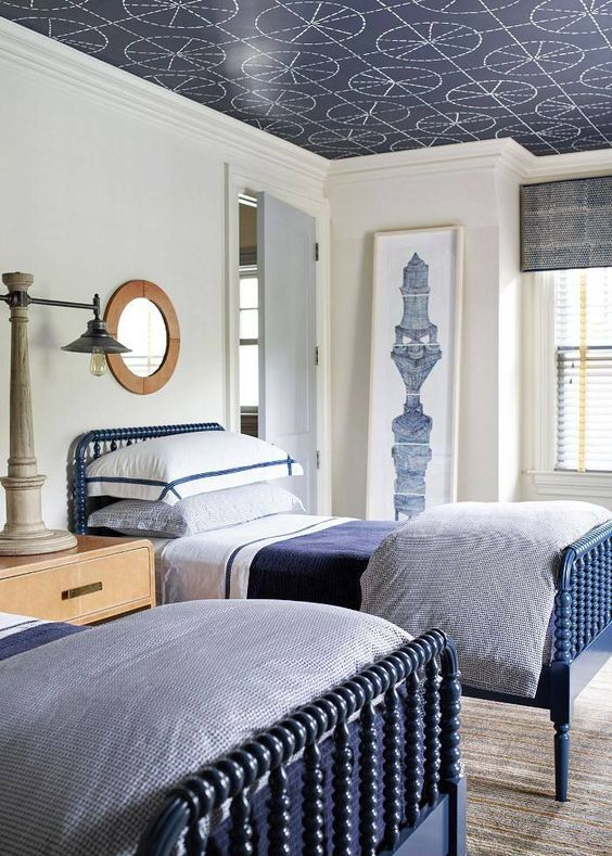 a stylish navy and white traditional shared teen bedroom with blue beds, wooden furniture and a printed ceiling