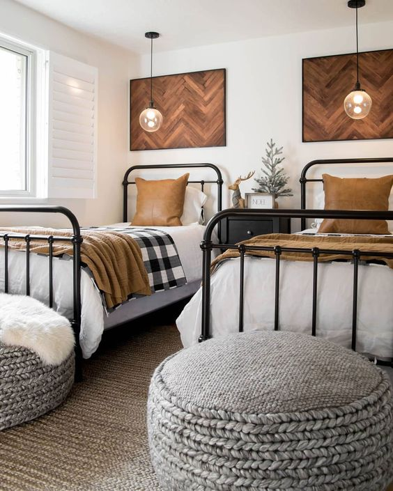 a stylish shared boy bedroom with chevron artworks, metal beds, knit ottomans and pendant lamps