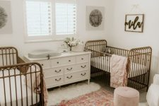 a stylish shared nursery with a vintage feel, with metal cribs, neutral furniture, a floral chandelier and printed rug
