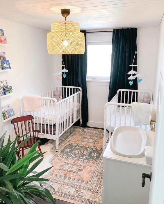 a stylish shared nursery with navy curtains, a boho rug, white furniture, a rattan lamp and cute cloud mobiles