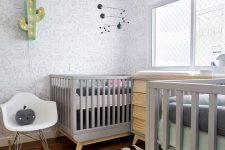 a stylish shared nursery with pinted wallpaper, grey and stained furniture, a printed rug and grey bedding
