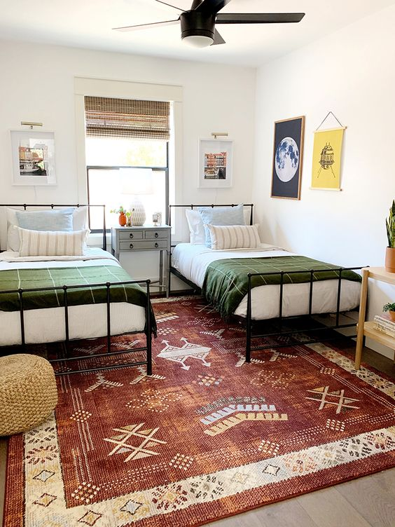 a stylish shared teen bedroom with metal beds, gallery walls, a printed rug and a wicker ottoman