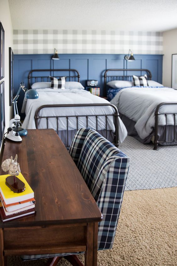 a stylish shared teen boy bedroom with black beds, a sained desk, a plaid accent wall and bedding