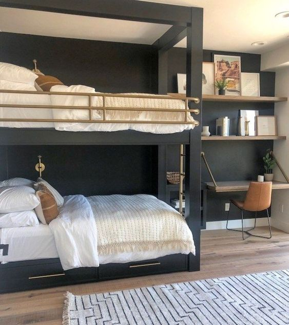 a stylish shared teen boy bedroom with black bunk beds, a folding desk, open shelves and touches of gold