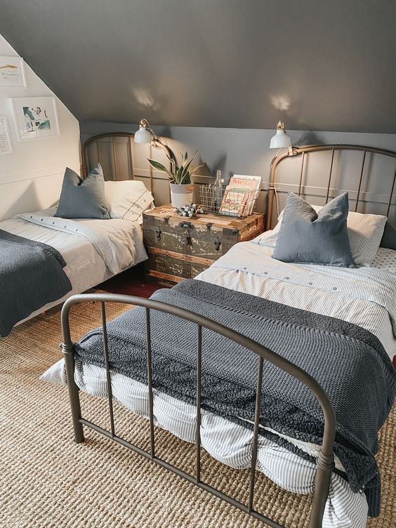 a stylish shared teen boy bedroom with metal beds, sconces, a vintage chest and a gallery wall