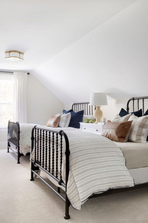 a stylish traditional attic shared bedroom with metal beds, a sideboard as a nightstand, printed bedding