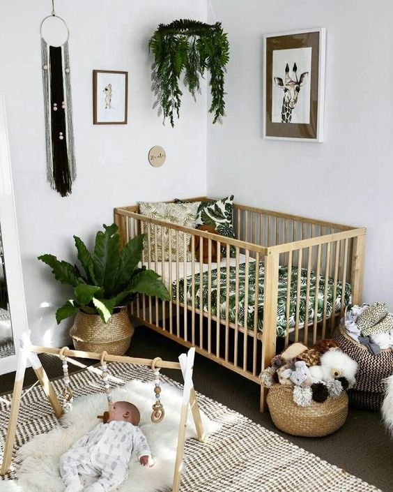 a tropical boho nursery with tropical bedding, baskets for storage, printed rugs, potted greenery is a stylish space