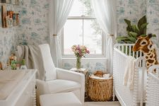 a tropical nursery with blue printed wallpaper, white furniture, a rattan stool, a beaded chandelier and a statement plant