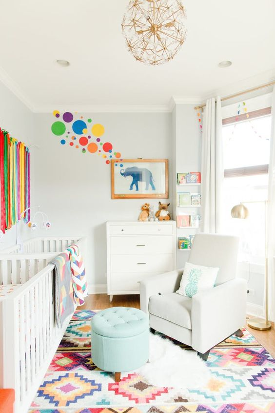 a vibrant shared nursery with white furniture, a colorful rug, ribbons and artworks on the wall and a floral chandelier