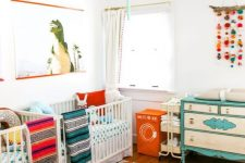 a vibrant twin nursery with colorful linens and bright furniture, a colorful mobile and an artwork