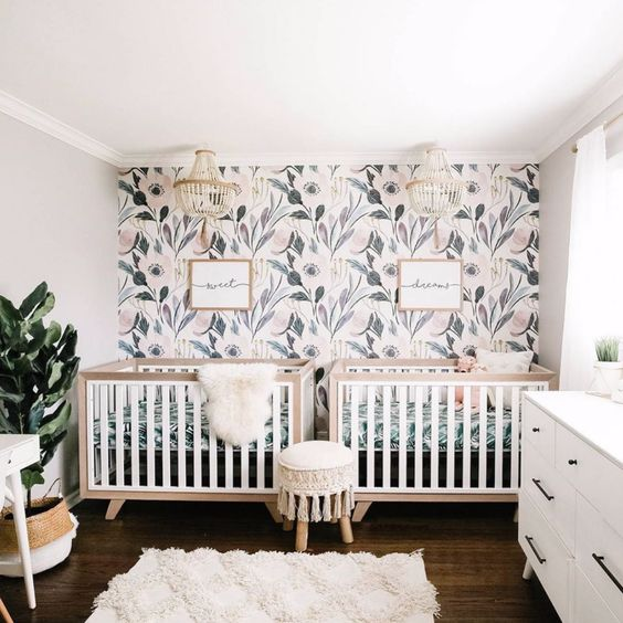 a welcoming neutral nursery with a botanical accent wall, neutral furniture, a potted plant and beaded chandeliers for decor