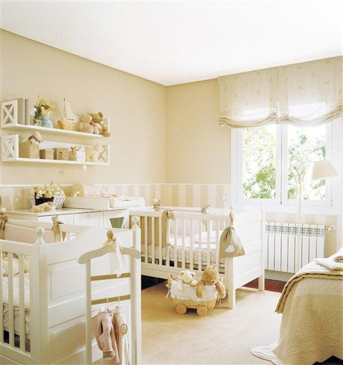 a welcoming neutral shared nursery with tan walls, white furniture and lots of toys everywhere