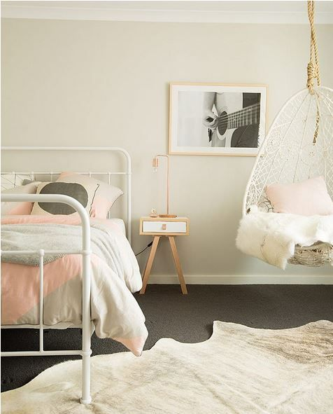 a welcoming teen girl bedroom in off-white, grey and light pink, with a pendant chair and printed bedding
