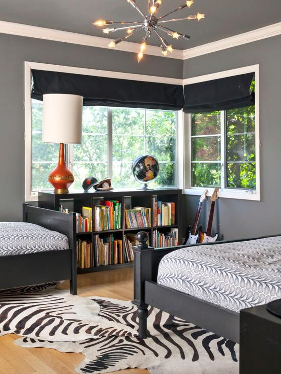 a whimsical shared boy bedroom with black curtains, black furniture, a faux animal skin rug and some lamps