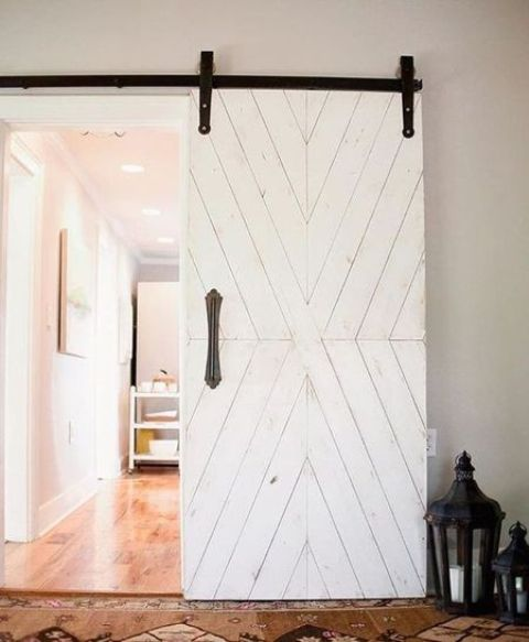 a white sliding vintage-inspired barn door for a rustic and vintage touch