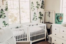 a woodland shared nursery with a tree statement wall, white furniture, artworks and much natural light