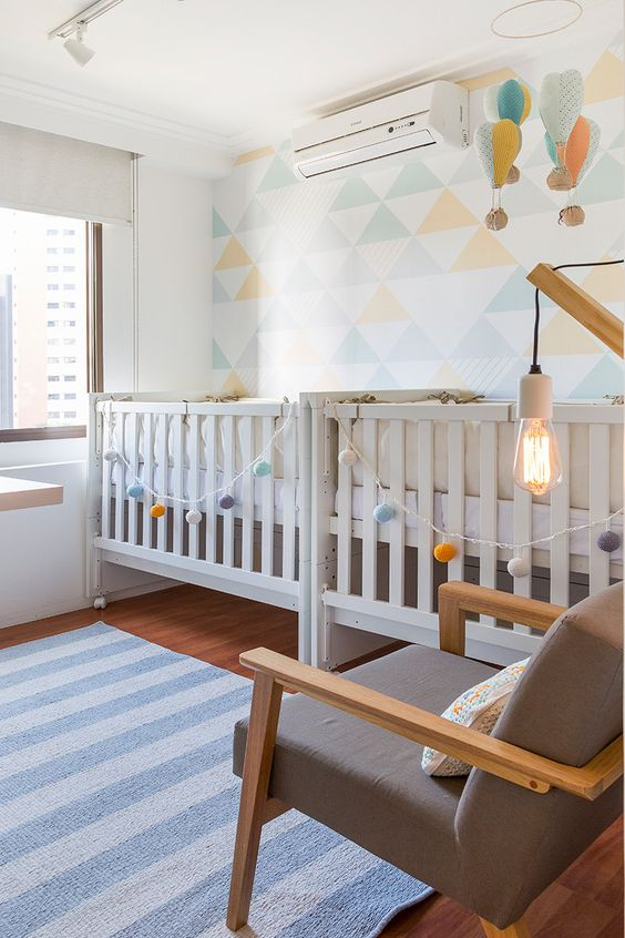 an airy and bright shared nursery with a geometric accent wall, hot air balloons and garlands and neutral furniture