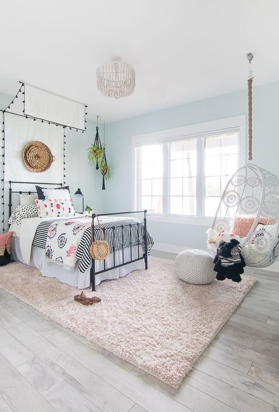 an airy boho teen girl bedroom with light blue walls, a bed with a cnaopy, printed bedding, a suspended chair and a blush rug