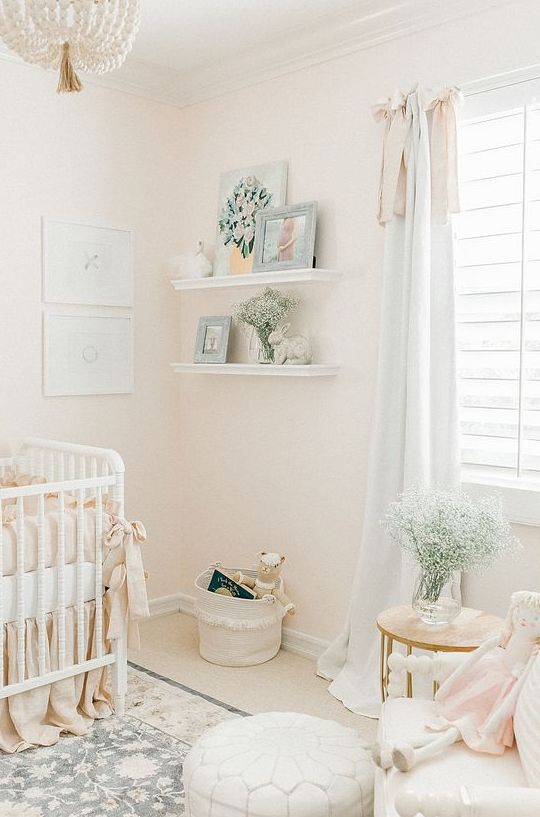 an airy neutral nursery with white furniture, open shelves, a mini gallery wall and a beaded chandelier is chic
