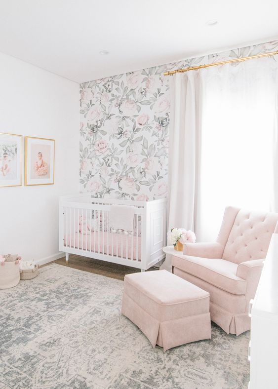 an airy nursery with a floral wall, a pink chair and ottoman, pink bedding and a boho rug is cool