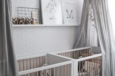 an all-neutral nursery with printed walls, white and stained furniture, grey canopies, a ledge with artworks and printed bedding