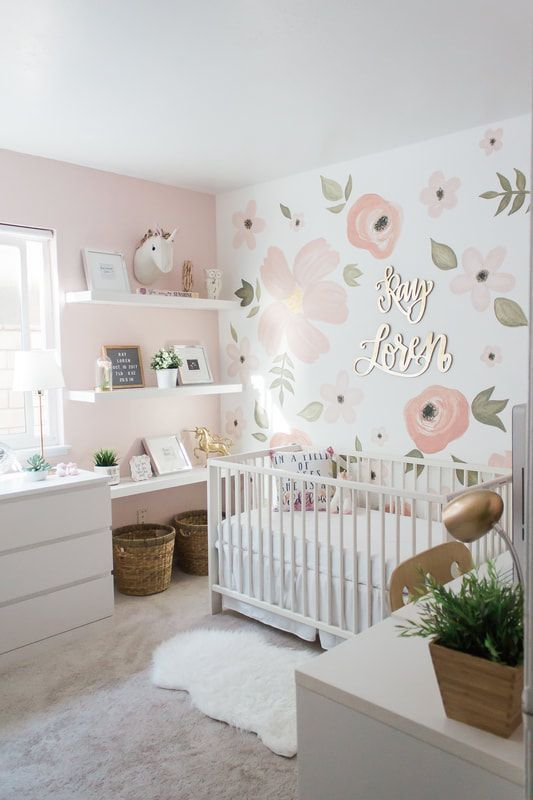 an amazing modern girl nursery with a floral accent wall, white furniture, gold and brass touches and potted greenery