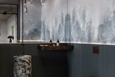 an arrangement of glass pendant lamps on chains is cool for a modern and industrial bathroom at the same time