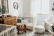 an elegant rustic nursery with white walls, a printed boho rug, white and stained furniture, a leather ottoman and a beaded chandelier
