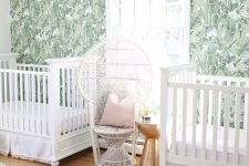 an ethereal boho nursery with a banana leaf wall, white furniture, a gold side table and white linens
