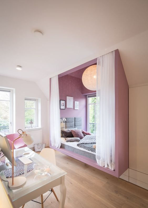 an ultra-modern and bold teen girl bedroom with a purple alcove sleeping space byt the window and a white studying zone