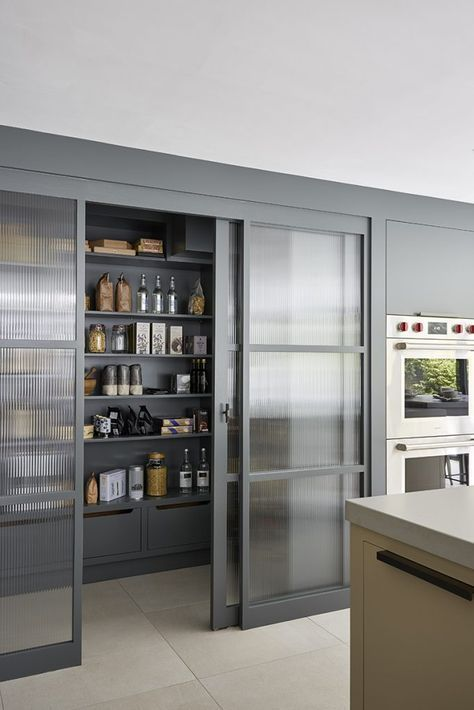 framed rain glass sliding doors hide the pantry and don't look bulky separating the spaces