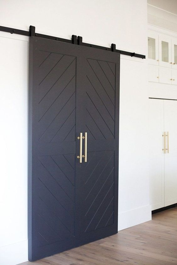 navy sliding barn doors with gold handles will bring a slight barn feel to the space and rustic touch