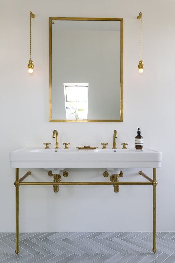 wall-mounted pendant lamps in gold match the vanity and the mirror frame and look chic