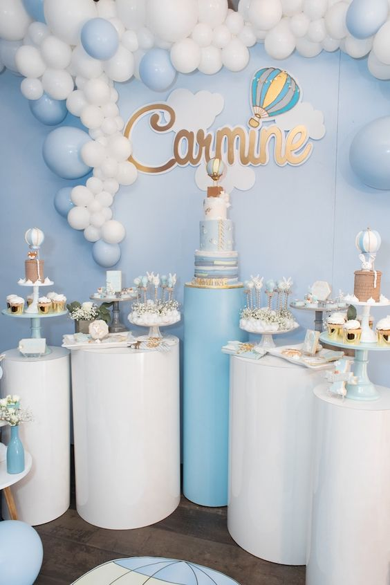 a blue and white pedestal dessert table with a hot air balloon backdrop, a balloon garland and lots of cute desserts