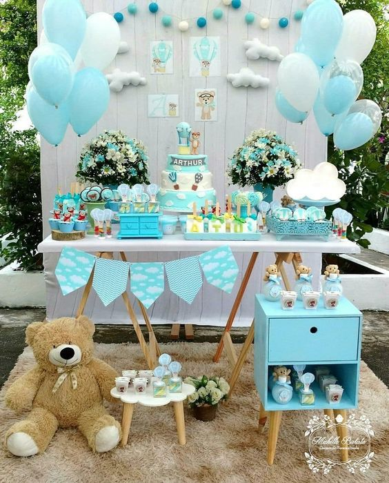 a blue dessert table with a backdrop done with clouds and blue balloons, a blue garland and blue and white floral arrangements