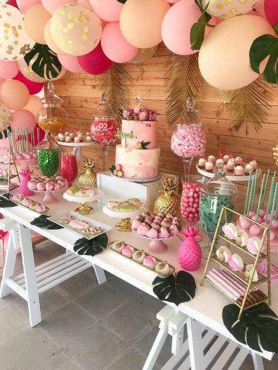 a bright pink, fold and fuchsia dessert table with a balloon garland over it, gilded tropical leaves, fake pineapples and jars and stands