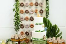 a jungle-themed dessert table with a donut wall, tropical leaves, lots of greenery and a large cake is a chic idea