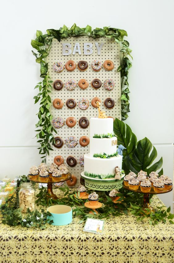 a jungle themed dessert table with a donut wall, tropical leaves, lots of greenery and a large cake is a chic idea