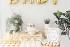 a neutral and gold baby shower dessert table with gold balloons, greenery arrangements and neutral desserts