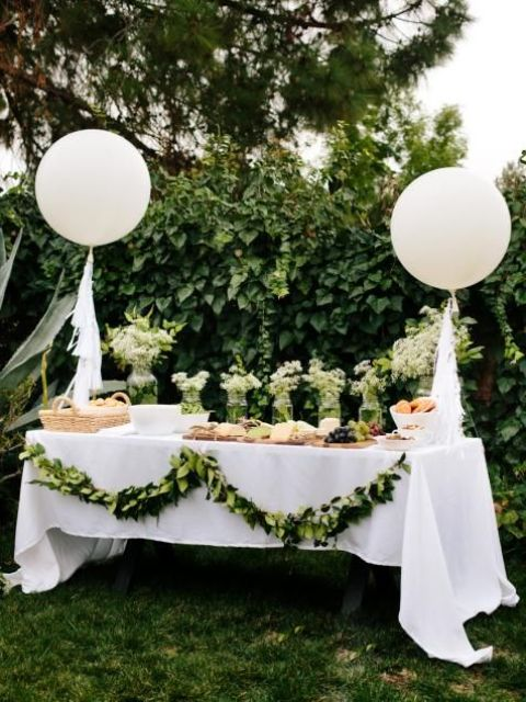 a neutral baby shower dessert table in white and green, with balloons and a greenery garland plus some neutral blooms