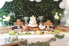 a neutral baby shower dessert table with a greenery backdrop, a large white balloon garland, a greenery garland and white blooms